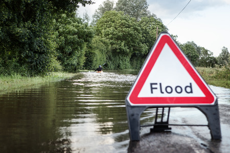 county road in essex of flooded road with a person paddling  down the road in a kayak Stock Photo