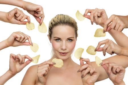 tempted: woman surrounded by hands holding crisps being  tempted to forget about the diet