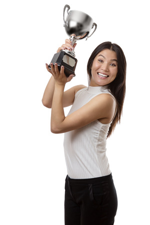 winning business woman: winning business woman holding a large trophy up in the air Stock Photo