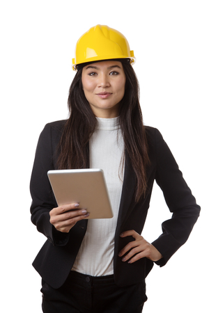 business woman wearing a hard hat looking at a plan on a tablet computer Stock Photo