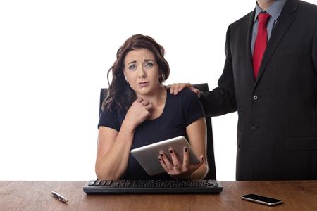 workplace harassment: mujer de negocios sentado en su escritorio con un compañero de trabajo de hombre tocando en el hombro Foto de archivo