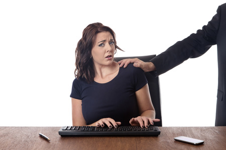 harassing: business woman sitting at her desk with a male work colleague touching her on the shoulder