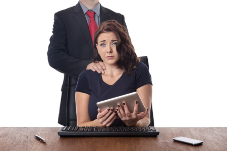 harassing: business woman sitting at her desk with a male work colleague touching her on the neck