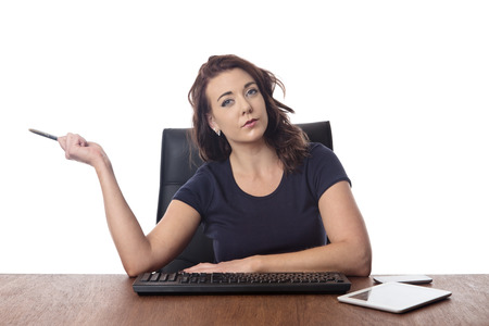 businesswoman sitting at desk looking confused