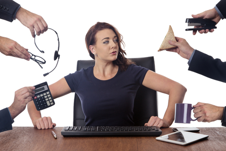 office stapler: business woman sitting at her desk surrounded by many hands holding different objects
