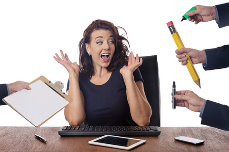 business woman sitting at her desk surrounded by many hands holding different objects