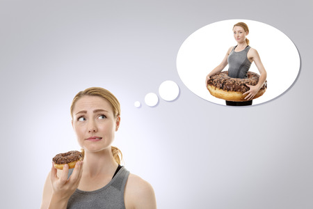 concept idea of a woman about to eat a donut but thinking she shouldnt really and it will not be good for the diet. Stock Photo