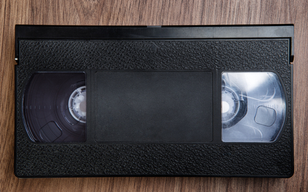 videocassette: old single cassette tape on wooden background looking down