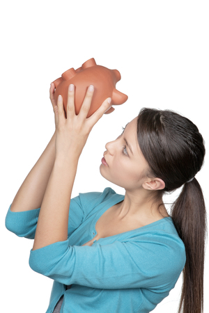 young woman turning her piggy bank upside down to see if she has any money left