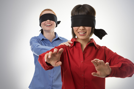 incapacity: two business woman blind folded leading the other