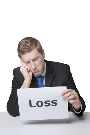 business man holding a paper sign with the word  loss written on it looking unhappy photo