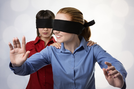 two business woman blind folded leading the other photo
