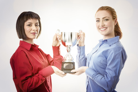 two business woman holding up a trophy photo