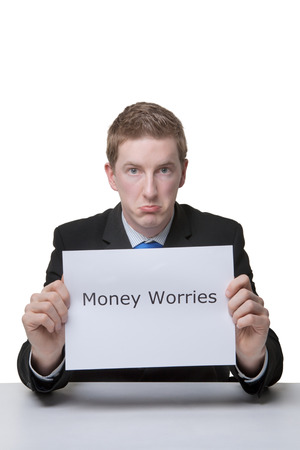 business man holding a paper sign with the words money worries written on it looking unhappy photo
