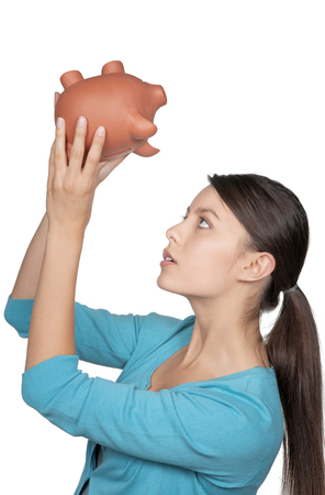 young woman turning her piggy bank upside down to see if she has any money left photo