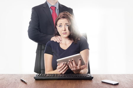 inappropriate: business woman sitting at her desk with a male work colleague touching her on the neck