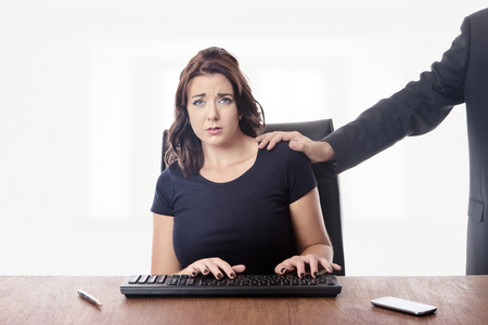 inappropriate: business woman sitting at her desk with a male work colleague touching her on the shoulder