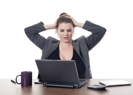 business woman at a desk stressed out pulling her hair out