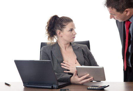 business woman sitting at her desk with a male colleague looking down her to at her breasts and cleavage
