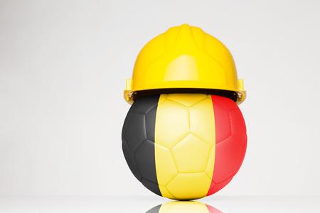 サッカー フットボールの上に重ねベルギー国旗とハード帽子をかぶって 写真素材