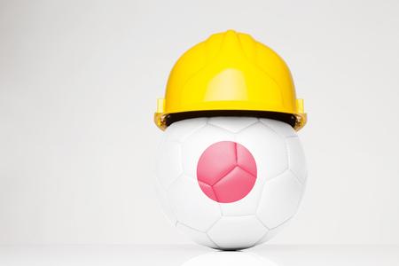 サッカー サッカーの上に重ね日本国旗とハード帽子をかぶって