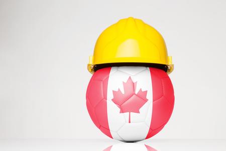 サッカー サッカーに重ね合わせられるカナダの国旗とハード帽子をかぶって 写真素材