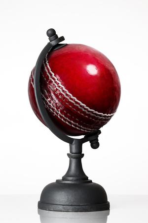 still life image of cricket ball world globe on white