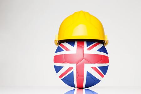 イギリス国旗のフットボールの上に重ね、ハード帽子身に着けているサッカー