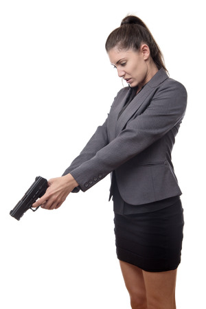 business woman pointing a gun down at something on the ground Stock Photo