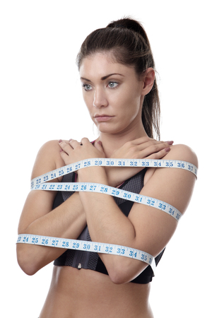 unhappy looking model with tape measures wrapped around her body Stock Photo