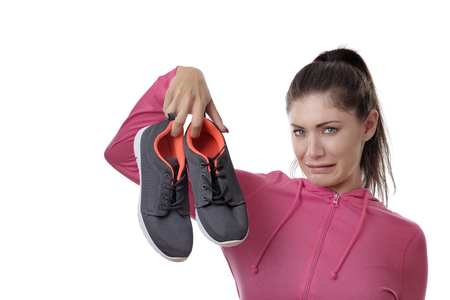 fitness woman holding up her smelly exercise shoes Stock Photo
