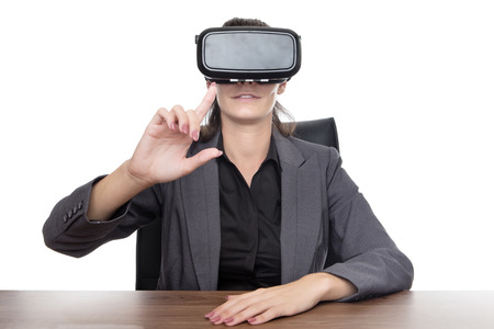 business woman sitting at desk working using a vr headset