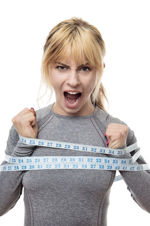 blond haired woman with a tape measure around her trying to break free from your restraints Stock Photo