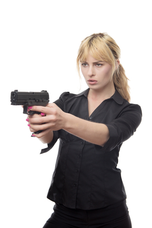 blonde haired business woman pointing a gun at the camera Foto de archivo