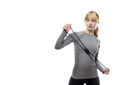 blonde haired woman wear a grey sports top using a rubber band for resistance training