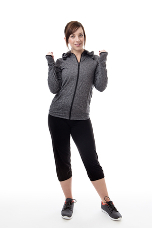 happy fitness woman wearing a tracksuit with her arm up in the air