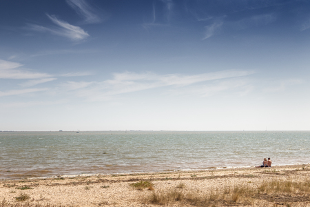 landscape images taken from a walk around the island of east mersea in essex england with two people sitting on the beach looking out to sea 免版税图像