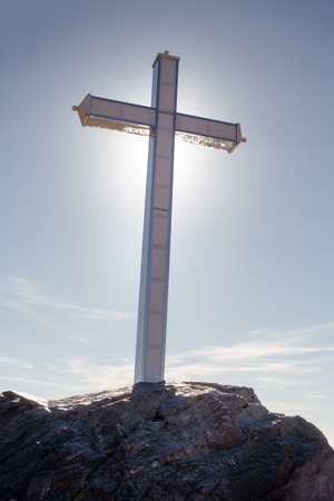 A large cross of  Penones del Santo in costa de tropical Almunecar spain, with the sun behind the cross