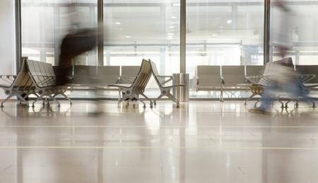 지나가는 사람들과 함께 비행기를 기다리는 공항 터미널 게이트 창가 의자 스톡 콘텐츠
