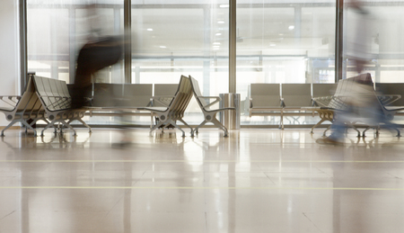 Stühle an einem Fenster eines Flughafenterminals warten auf den Flug mit Passanten Standard-Bild