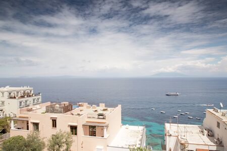 roof top image of building on the island of capri in italy with a view of mount vesuvius in the background across the sea