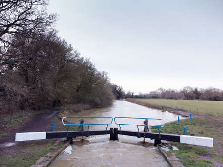 high water overflowing over a lock in essex englang after a lot of rainfall