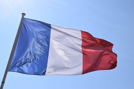 French flag waving on a sunny day. Big flag on a pole in France. Patriotic symbol in Paris.
