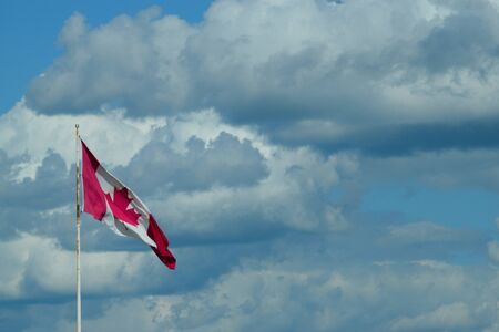 Canadian flag on a pole with a cloudy sky in the background. Maple leaf red and white flag of Canada.