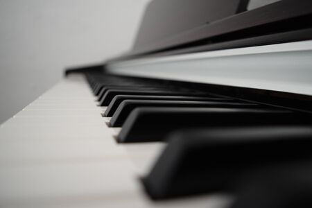 Piano keyboard with a white background. Classical music playing. Close up of keys.