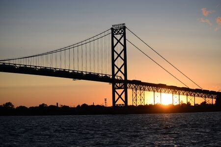 Ambassador bridge silhouette at sunset. Detroit and Canada border bridge. International crossing