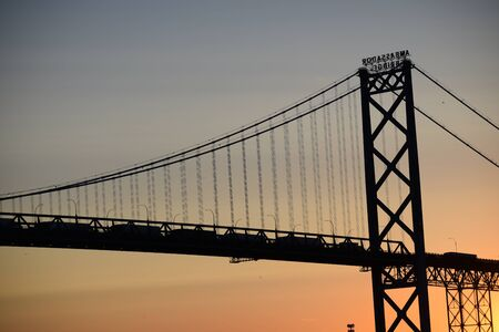 Silhouette of the Ambassador Bridge at sunset. USA and Canada border over the Detroit River