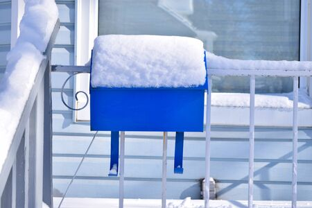 Blue mailbox with space for text. Mail box on a porch in front of a blue house, during a winter snow day. Banque d'images