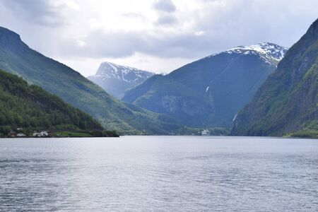 Norway fjord on a cloudy day, with mountains with snow n the background