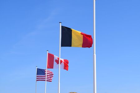 Belgian, Canadian and American flags waving on a blue sky. WW2 allies symbol
